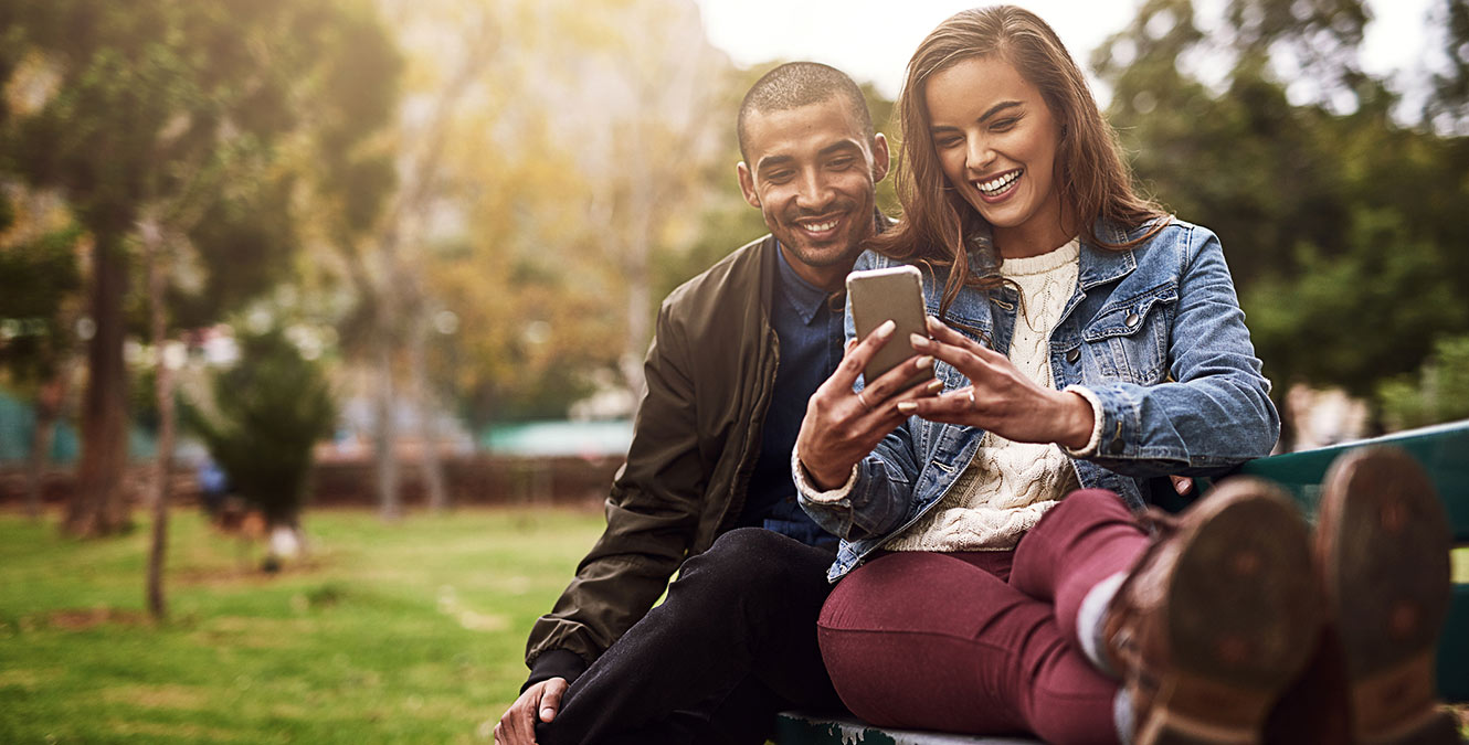 Young couple looking at phone in park.